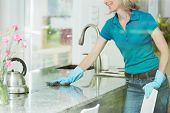 Woman Wiping Down Kitchen Countertop poster