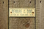 Beware Of The Dog Sign On A Wooden Fence.