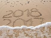 2018 and 2017 year date handwritten on the beach. New Year 2018 replacing Old Year 2017 being washed poster