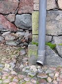 Drainpipe against old stone wall