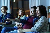 friendship and leisure concept - friends with popcorn and remote control watching tv at home at nigh poster