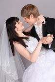 image of wedding couple  - Groom and beautiful bride dance in studio on gray background - JPG