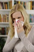 Woman with flu or allergy sneezing at home