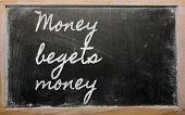 Expresión - dinero genera dinero - escrito en una pizarra con tiza de escuela