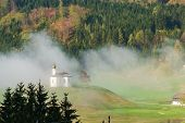 Small Church On Hill In Fog. Alpine Landscape With Small Church In Fog. Morning Fog Covering Small C poster