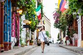Beautiful Woman On White Dress Walking Alone At The Colorful Streets Of The Colonial Walled City Of poster