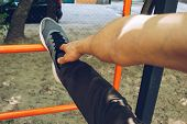 Male Athlete In Running Sports Shoes Standing Stretches His Leg On The Sports Field With A Metal Lad poster