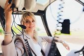 Female Pilot In Cockpit Of Helicopter Before Take Off. Young Woman Helicopter Pilot. poster