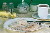 foto of biscuits gravy  - A very country breakfast of pork chop with biscuits and gravy served in old - JPG