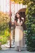 Beautiful Teen Girl In Glamorous Golden Dress Standing By The Gate.  Waiting For Her Prom Date poster