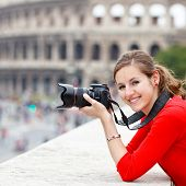 Portrait of a pretty young tourist taking photographs while sightseeing in Rome, Italy (with Colosseum in the background)