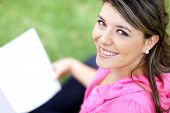 Beautiful young woman studying with a book at the park