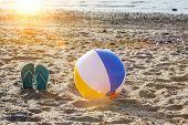 Flip flops on beach sand with beach ball and sun poster