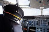 stock photo of cabin crew  - Captain pilot hat inside an airplane cabin - JPG