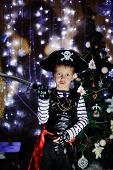 picture of plunder  - The boy in clothes of the pirate against a New Year tree poses - JPG