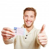 Happy man with his European drivers licence holding his thumbs up