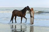 dreamy shot of woman in the ocean with her horse, time exposure with wave motion