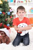Little boy sits near Christmas tree with gift in hands