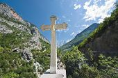 crucifix on the background the Kelmend mountains; the cross bears witness to the Catholic faith predominant in the mountainous regions in the north of Albania