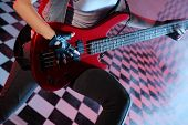 Part of body of woman playing electric guitar in studio with checkered background in smoke and purple light.