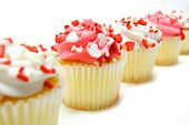 image of sprinkling  - Row of pink and white Valentines Day cupcakes with sprinkles over white - JPG