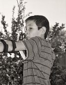 stock photo of fletching  - Close up of a young boy drawing back a bow and arrow - JPG