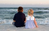 image of little boy  - Little boy and girl sit at the beach and watch the waves roll in at sunset - JPG