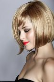 beautiful young woman with short blond hair in a bob wearing red lipstick on studio background