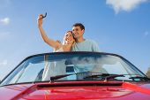 Cheerful couple standing in red cabriolet taking picture on a sunny day