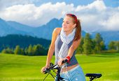 Portrait of cute cyclist girl resting in mountains, traveling on bicycle along Austrian mountains, enjoying beautiful nature, freedom concept