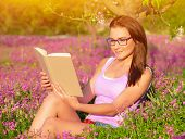 Attractive student girl sitting on pink floral field and read book, doing homework outdoors, wearing glasses, education concept