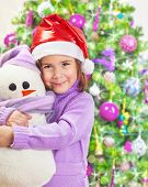 Beautiful little happy girl wearing red Santa hat and holding in hands snowman soft toy, Christmas tree, happy winter holidays