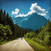 Motorcyclist riding on mountainous highway, Euro tour on motorbike, road pass along Alps mountains,