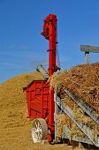 picture of threshing  - the threshing machine is adding to the straw pile