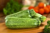 picture of zucchini  - Raw zucchini on wooden board with other ingredients in the back  - JPG