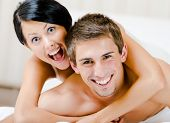 Close up view of laughing couple who plays in bedroom. Woman lying on the back of the man embraces him