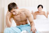 Young couple argues in bed. Depressed young man sitting on the edge of the bed. Focus on man