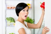 Young woman takes red pepper from the opened fridge full of vegetables and fruit. Concept of healthy