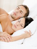 Couple sleeping in bedroom under white eiderdown
