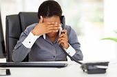 tired african american businesswoman using landline phone