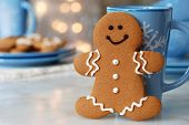 Smiling gingerbread man standing next to snowflake mug.  Plate of additional cookies and defocused holiday lights in background.  Closeup with shallow dof.  Copy space included for text.