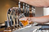 Mans hand pouring pint of beer behind the bar