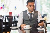 Attractive businessman sitting in restaurant and using his phone