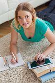 Cheerful young woman lying on floor using tablet to do her assignment looking at the camera