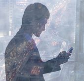Young businessman using mobile phone, double exposure over city traffic at night