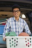 Portrait of boy with college dorm items in back of car