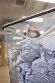 Businessman preparing to throw paper into wastepaper bin, close up on wastepaper bin
