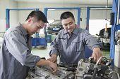 Two Mechanics Working on Car Engine
