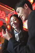 Coworkers using smart phone at night, City street, red lanterns on the background
