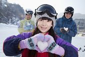 Family in Ski Resort, Daughter Showing Snow Heart